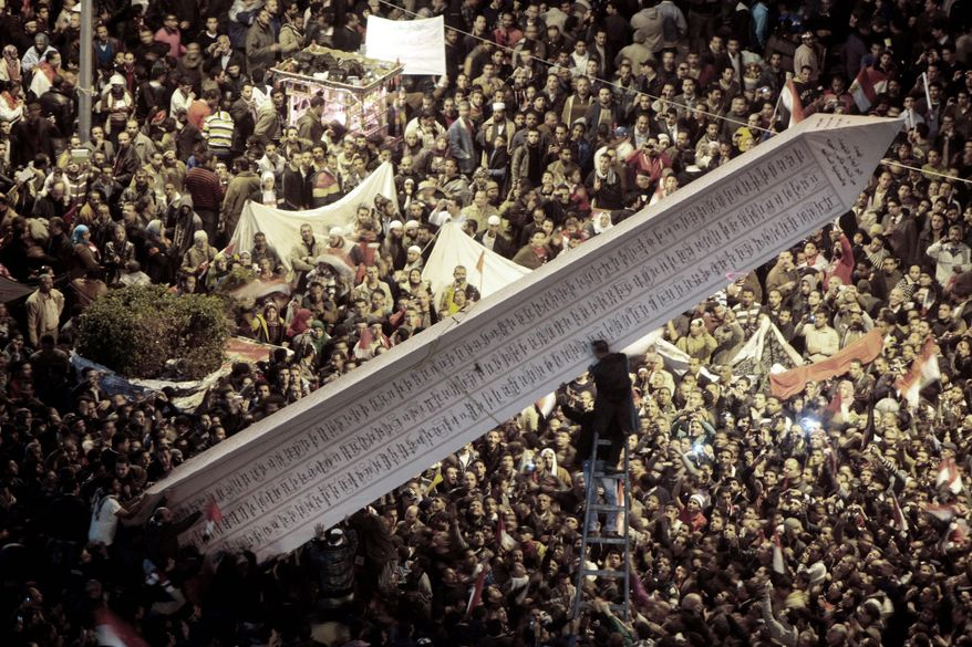 Egyptians set up an obelisk with the names of people who were killed during the 18-day uprising as they marked in Cairo's Tahrir Square on Wednesday the first anniversary of the start of the revolt that forced President Hosni Mubarak from power. (Associated Press)