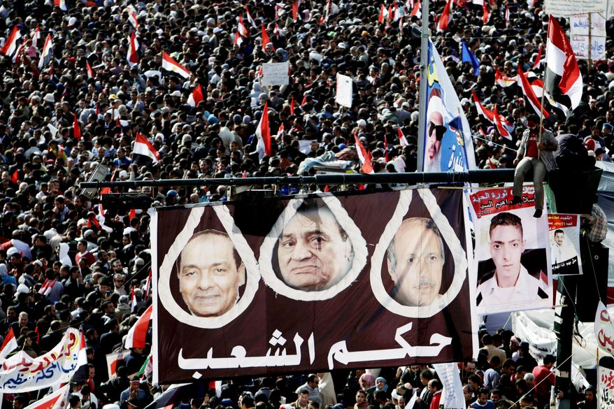 """Egyptian protesters hold a large banner depicting Gen. Hussein Tantawi, left, former President Hosni Mubarak, center, and former interior minister Habib al-Adly in nooses with Arabic writing that reads, """"The peoples rule,"""" in Tahrir Square during a rally to mark the one year anniversary of the uprising that ousted President Hosni Mubarak in Cairo, Egypt, Wednesday, Jan. 25, 2012. Tens of thousands of Egyptians rallied Wednesday to mark the first anniversary of the country's 2011 uprising, with liberals and Islamists gathering on different sides of Cairo's Tahrir Square in a reflection of the deep political divides that emerged in the year since the downfall of longtime leader Hosni Mubarak. The graffiti at right, in Arabic, reads, """"freedom,"""" and """"down with the military rule.""""(AP Photo/Muhammed Muheisen)"""