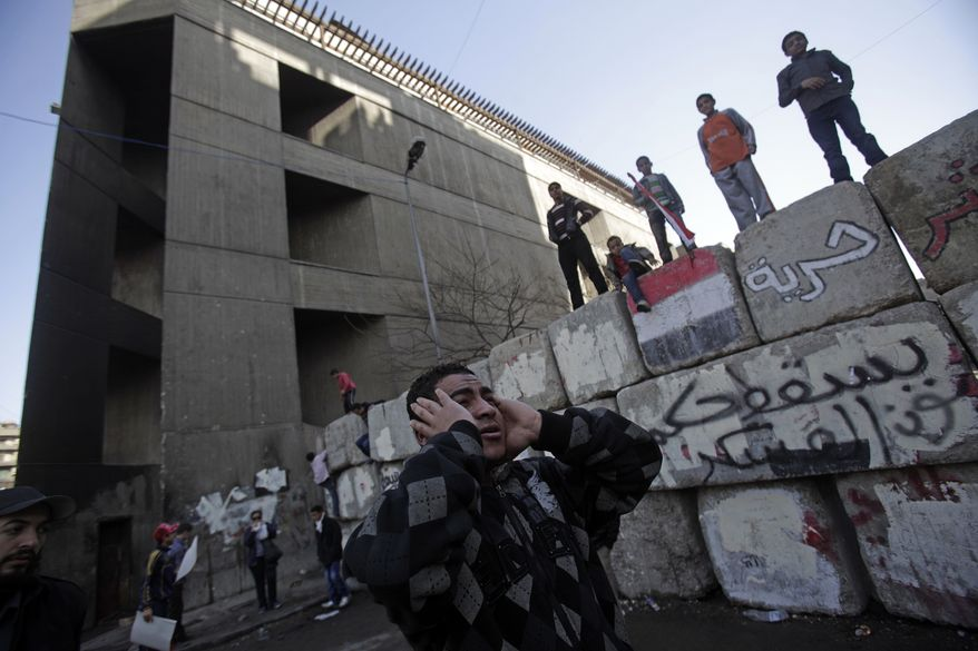 A man prays next to a security barrier in Tahrir Square during a rally to mark the one year anniversary of the uprising that ousted President Hosni Mubarak in Cairo, Egypt, Wednesday, Jan. 25, 2012. (AP Photo/Muhammed Muheisen)