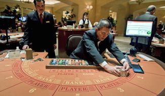 Baccarat dealer Ramiro Nepomuceno (right) shuffles cards as floor supervisor Sam Insyxiengmay looks on while preparing a table for play at the MGM Hotel and Casino on Wednesday in Las Vegas. Baccarat, popular with Asian high rollers, is the most profitable table game for casinos. (Associated Press)