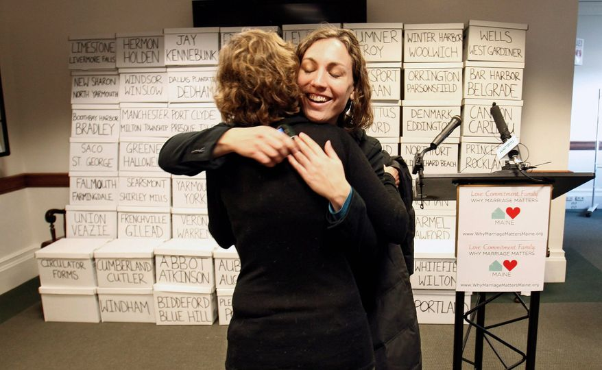 Ali Vanderzanden, with Equality Maine, hugs a friend before a Thursday news conference at the Statehouse in Augusta, Maine, at which a bid to legalize gay marriage in Maine was launched. (Associated Press)