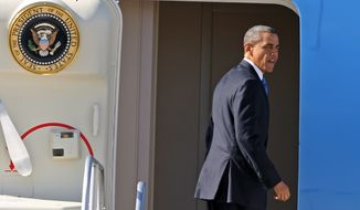 President Obama turns to wave Jan. 26, 2012, as he boards Air Force One departing Las Vegas after spending the night. He spoke about energy innovations and promoted alternative fuels that day at a United Parcel Service hub in Las Vegas (Associated Press)