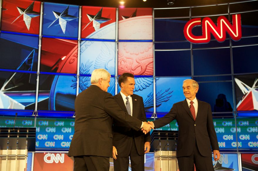 Republican presidential candidates (Left to Right) former House Speaker Newt Gingrich, former Massachusetts Governor Mitt Romney and Rep. Ron Paul (R-Tex) shake hands as they arrive on stage for the Florida Republican Presidential Debate at the University of North Florida in Jacksonville, Fla., Thursday, January 26, 2012. This is the second and final debate before the Florida Republican primary on Tuesday, January 31, 2012. (Rod Lamkey Jr/ The Washington Times)