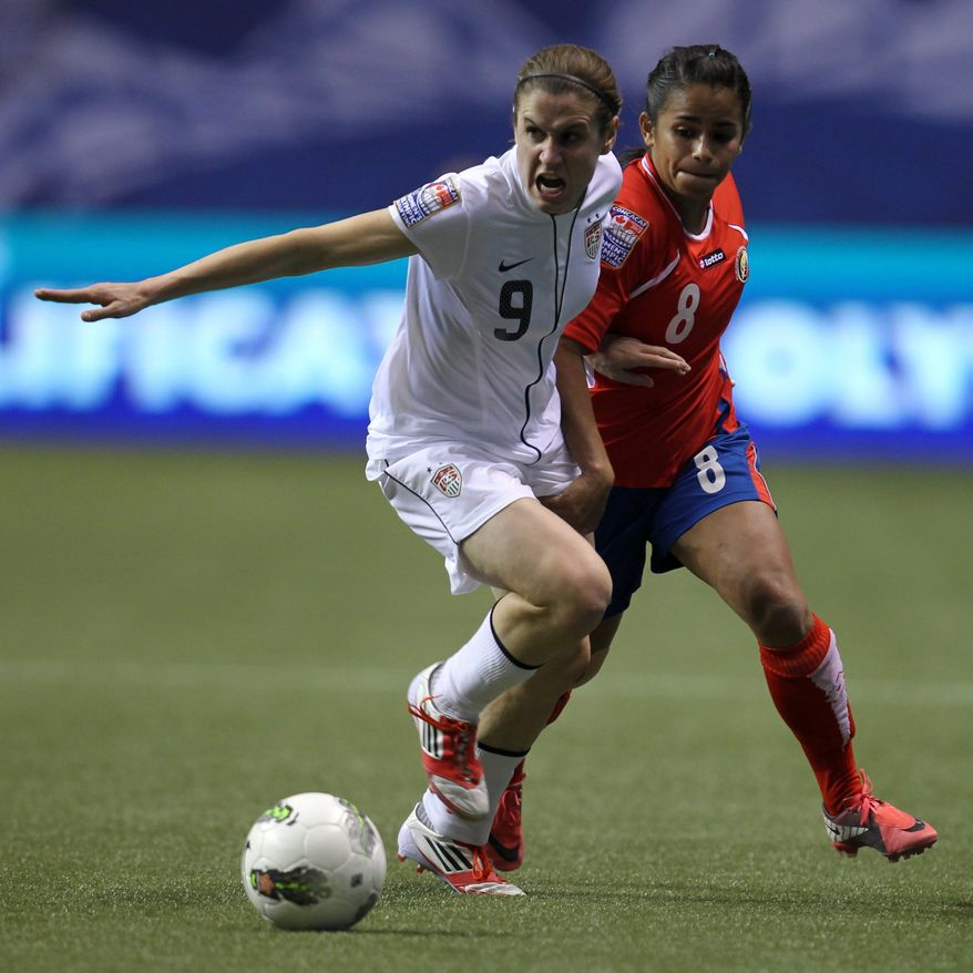 United States' Heather O'Reilly fights for control of the ball with Costa Rica's Daniela Cruz during the second half of CONCACAF women's Olympic qualifying soccer game action at B.C. Place in Vancouver, British Columbia, Friday, Jan. 27, 2012. (AP Photo/The Canadian Press, Jonathan Hayward)