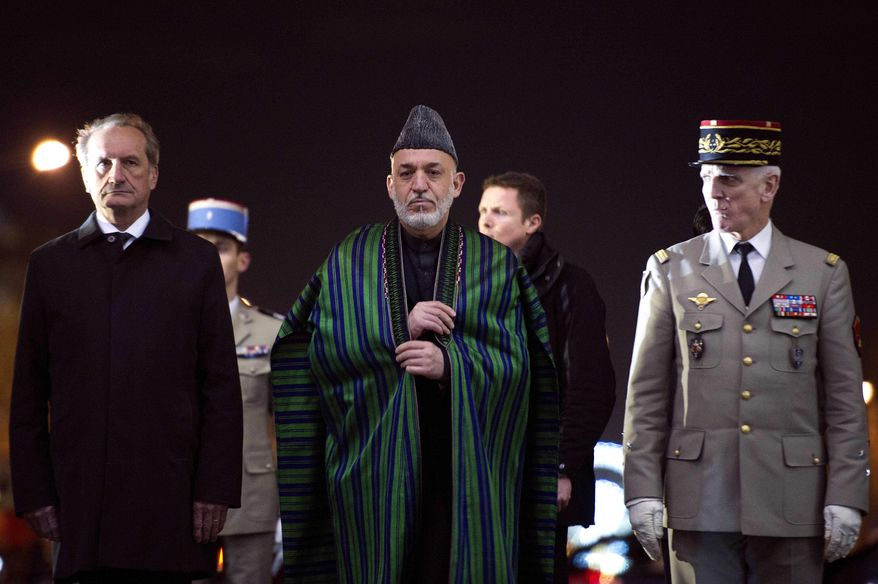 Afghanistan's President Hamid Karzai, center, France's Defense and Veterans Minister Gerard Longuet, left, and French General and Paris military governor Bruno Dary, right, pay tribute to the Unknown soldier's tomb, at the Arc of Triomphe, in Paris, Friday Jan. 27, 2012. (AP Photo/Lionel Bonaventure, Pool)