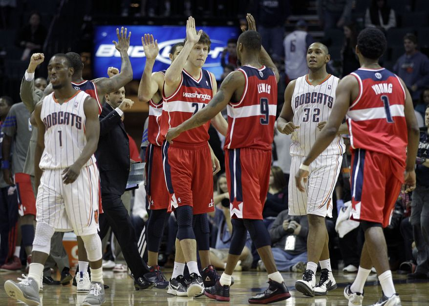 Washington Wizards' Rashard Lewis (9), Jan Vesely (24), and Nick Young (1) celebrate as Charlotte Bobcats' Kemba Walker (1) and Boris Diaw (32) walk off the court after the Wizards' 102-99 win in Charlotte, N.C., Saturday, Jan. 28, 2012. (AP Photo/Chuck Burton)