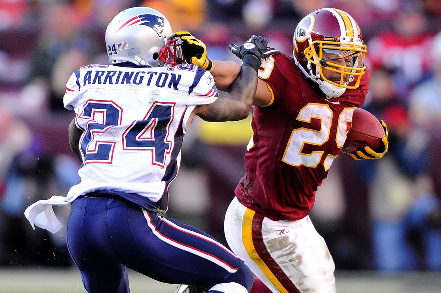 Washington Redskins running back Roy Helu (29) pushes off of New England Patriots cornerback Kyle Arrington (24) during an 8-yard run in the third quarter at FedEx Field in Landover, Md., on Sunday, December 11, 2011. (Preston Keres/Special to The Washington Times)