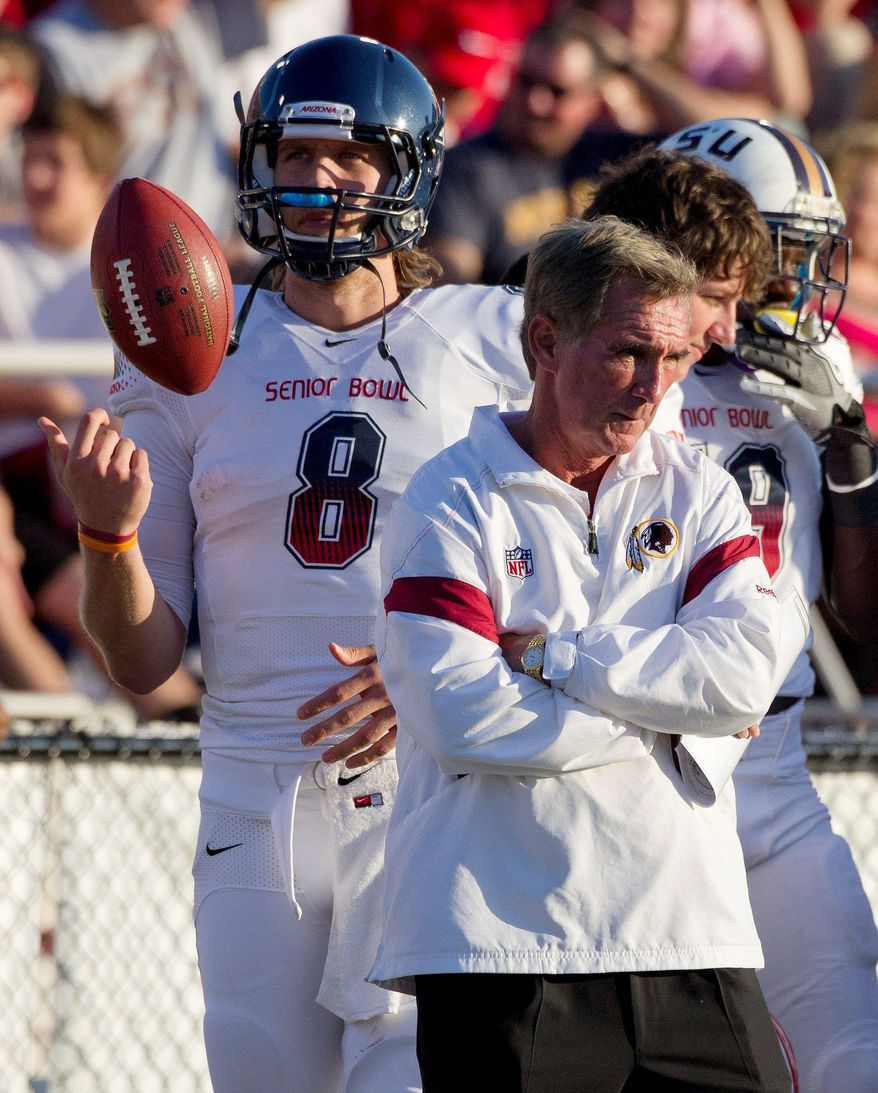 South squad coach Mike Shanahan of the Washington Redskins, watches from the sidelines with South Squad quarterback Nick Foles (8) of Arizona, in the first half of the Senior Bowl NCAA college football game at Ladd-Peebles Stadium in Mobile, Ala., Saturday, Jan. 28, 2012. (AP Photo/Dave Martin)