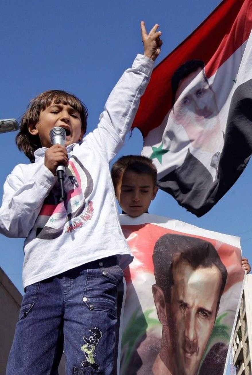 Youngsters show support for the Syrian regime and gratitude toward Moscow on Sunday in front of the Russian Embassy in Beirut. Russia has said it will use its Security Council veto to block any resolution threatening Syria. (Associated Press)