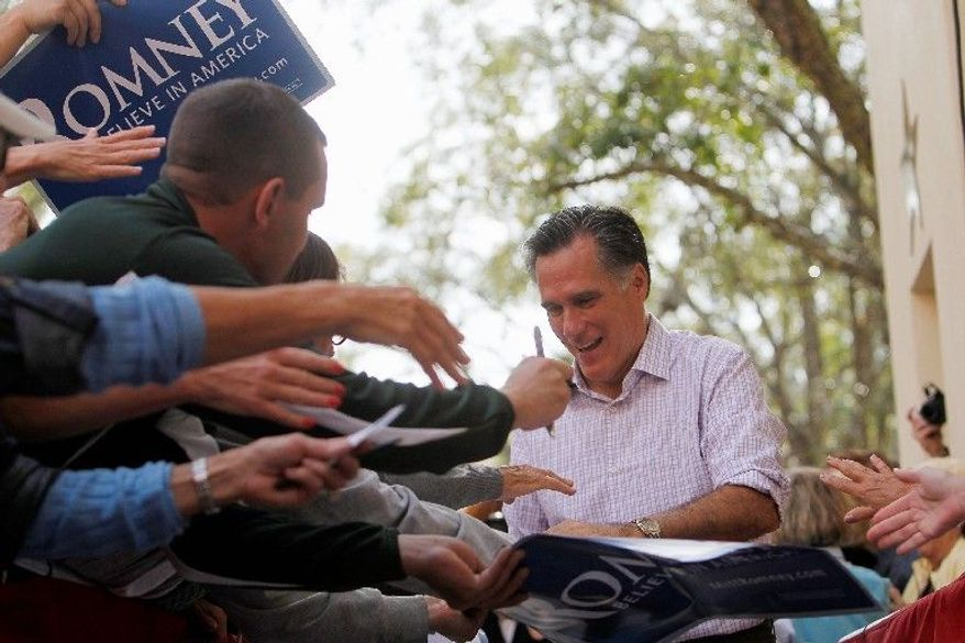 Republican presidential hopeful Mitt Romney signs autographs after addressing a crowd of supporters during a campaign rally Sunday in Naples, Fla., ahead of Tuesday's state GOP primary. The former Massachusetts governor has sought to distance his health care law in the Bay State from President Obama's national law. (Naples Daily News via Associated Press)