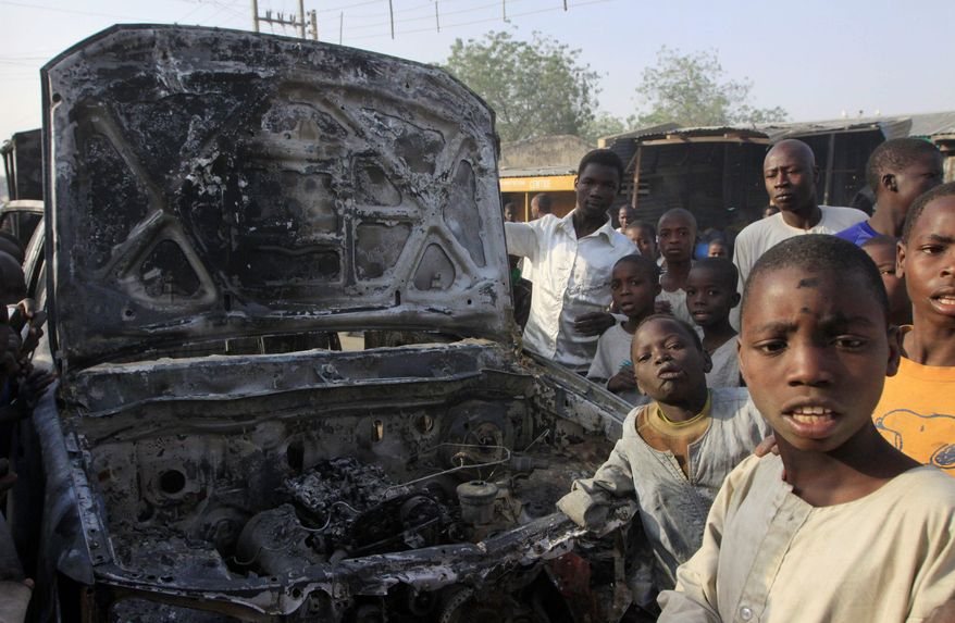 Children gather around a scorched police truck after an attack at a police station in Kano, Nigeria, last week. Youths overran the police station in the Sheka neighborhood that morning. (Associated Press)