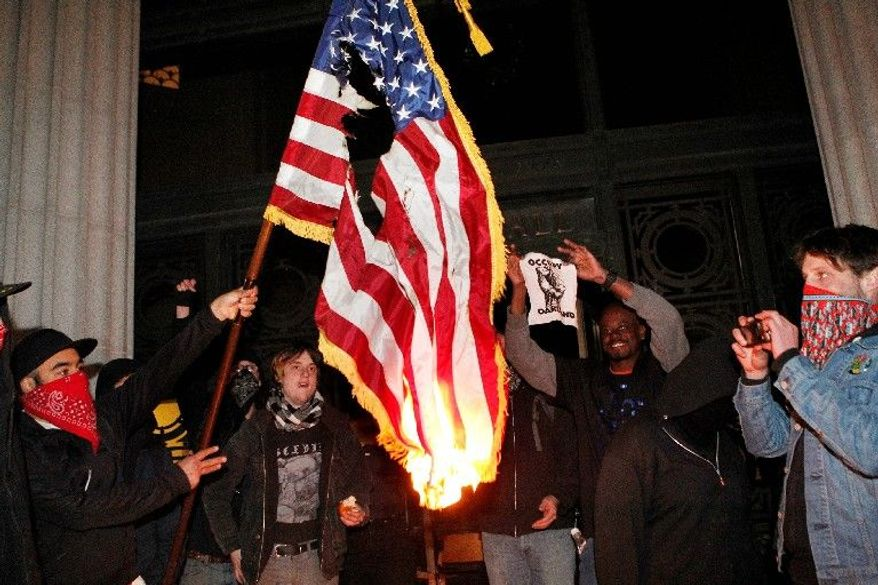 Occupy Oakland protesters burn a flag found inside Oakland, Calif., City Hall on the steps of the municipal building Saturday. (Associated Press)
