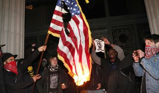 Occupy Oakland protesters burn an American flag found inside City Hall on Saturday, Jan. 28, 2012, in Oakland, Calif. (AP Photo/Beck Diefenbach)