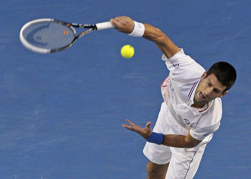 Novak Djokovic of Serbia serves to Rafael Nadal of Spain during the men's singles final at the Australian Open tennis championship in Melbourne, Australia, on Sunday, Jan. 29, 2012. (AP Photo/John Donegan)