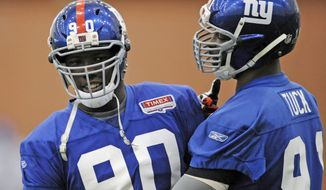 New York Giants defensive ends Jason Pierre-Paul, left, and Justin Tuck meet during NFL football practice on Friday, Jan. 27, 2012, in East Rutherford, N.J. The Giants face the New England Patriots in Super Bowl XLVI on Feb. 5 in Indianapolis. (AP Photo/Bill Kostroun)