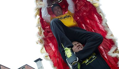 Jason Lee, top, of Silver Spring, Md., is lifted in a Futshan lion mask as he and other members of the Chinese Youth Club practice their lion dance before the Chinese New Year parade. (Barbara L. Salisbury/The Washington Times)