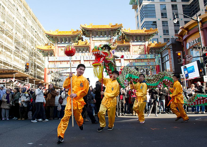 With hundreds of people lining the streets under the Chinatown arch, Zikuan Li, 17, of Clifton, David White, 15, of Great Falls, Michael Qu, 16, of Centreville, and Kevin Liu, 14, of Fairfax, all members of the New World Bilingual Institute, parade their dragon in the streets during the Chinese New Year Parade. (Barbara L. Salisbury/The Washington Times)