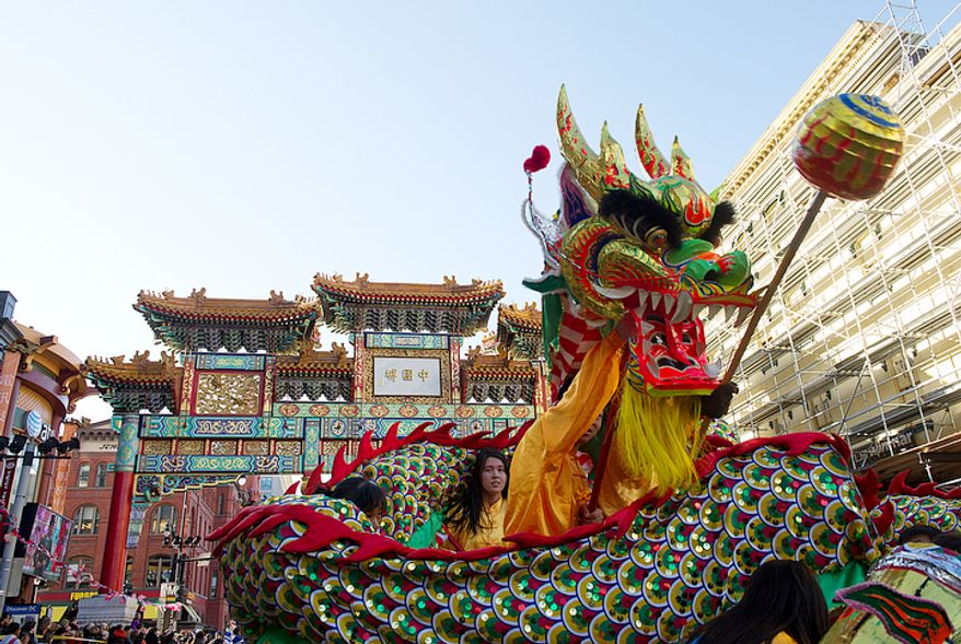 The New World Bilingual Institute's dragon makes its way under the Chinatown arch during the Chinese New Year Parade in Washington, D.C.,on Sunday, Jan. 29, 2012. (Barbara L. Salisbury/The Washington Times)