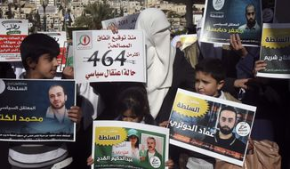Palestinian Hamas supporters hold banners of prisoners arrested by the Palestinian Authority and call for their release during a protest in the West Bank city of Nablus on Monday, Jan. 9, 2012. (AP Photo/Nasser Ishtayeh)