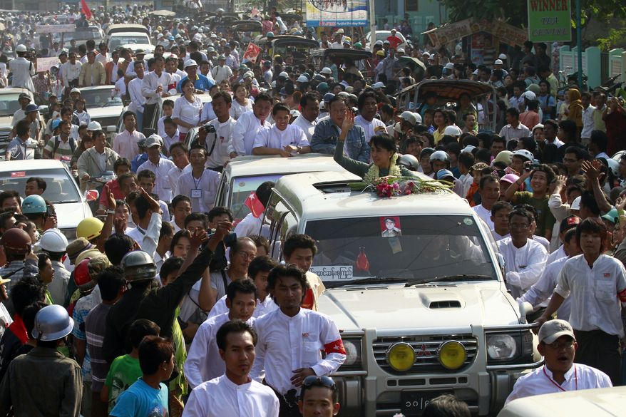 Myanmar pro-democracy leader Aung San Suu Kyi (center) waves to supporters on her arrival in Dawei, Myanmar, on Sunday, Jan. 29, 2012. Thousands of supporters in Myanmar's countryside cheered Mrs. Suu Kyi as she made a political tour ahead of parliamentary by-elections. (AP Photo/Khin Maung Win)