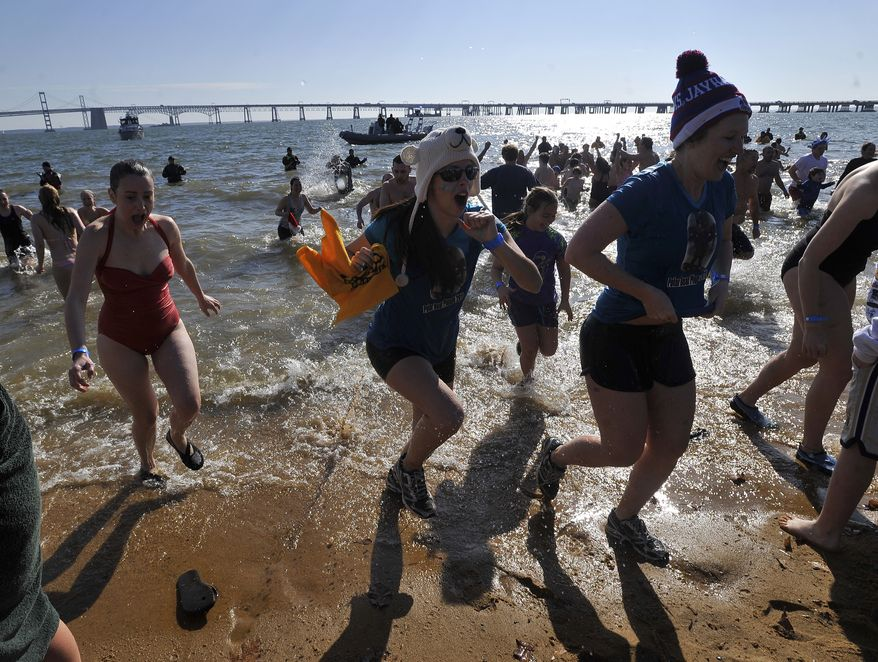 A group of plungers, including Lizzie Evans (center), run out of the Chesapeake Bay during the 16th annual Polar Bear Plunge to raise funds for the Special Olympics Maryland on Saturday, Jan. 28, 2012, in Annapolis. (AP Photo/Gail Burton)