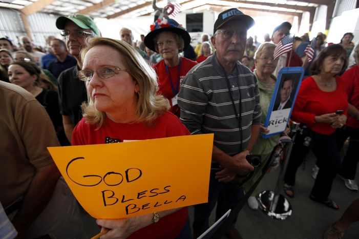 Sharon Irwin holds a sign during a prayer for Bella, a daughter of Republican presidential candidate and former Pennsylvania Sen. Rick Santorum, during a campaign rally in a hanger at Sarasota Bradenton International Airport in Sarasota, Fla., on Sunday, Jan. 29, 2012, where Mr. Santorum was scheduled to appear. He was staying home in Philadelphia to be with 3-year-old Isabella, who is hospitalized. (AP Photo/Paul Sancya)
