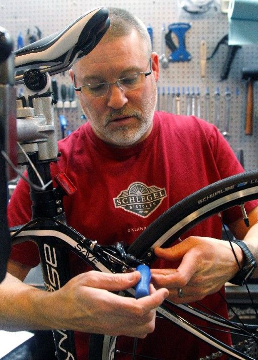 Steve Schlegel, owner of Schlegel Bicycles, works on a bicycle in the shop's pro shop in Oklahoma City on Thursday. In Oklahoma, Republican Gov. Mary Fallin says gradually cutting the top income-tax rate of 5.25 percent will make the state more attractive to businesses, help spur economic growth and ensure Oklahoma is competitive against neighboring states such as Texas. (Associated Press)