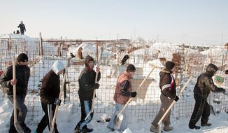 Inmates from the Jilava prison in Romania are mobilized Monday in 5 degrees Fahrenheit to dig out a snowed-in shelter for stray dogs in nearby Glina. Temperatures plunged to minus 16.6 in some parts of Romania and -15 F in Poland. At least 36 deaths in Eastern Europe were blamed on the cold. (Associated Press)