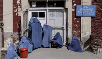 **FILE** An Afghan woman (center) peeks inside a hospital on the outskirts of Kabul, Afghanistan, on Oct. 26, 2011, while she and others wait for an employee to let them enter. (Associated Press)