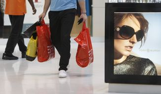 A shopper carries purchases Nov. 9, 2011, while shopping at Dolphin Mall in Miami. (Associated Press)