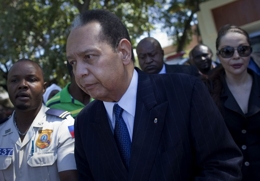 "** FILE ** Former Haitian dictator Jean-Claude ""Baby Doc"" Duvalier leaves the courthouse with his longtime companion, Veronique Roy (right), after attending a closed hearing in Port-au-Prince, Haiti, on Friday, Jan. 20, 2012. (AP Photo/Ramon Espinosa, File)"