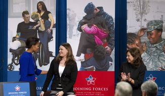 First lady Michelle Obama greets RyAnne Noss at the Labor Department in Washington on Monday, Jan. 30, 2012, where Mrs. Obama announced a proposed rule to help caregivers of wounded, ill and injured service members and veterans. Mrs. Noss left school to take care of her husband, SFC Scot Noss, who was injured in Afghanistan in February 2007 during his eighth tour of duty as an Army Ranger. At right is Labor Secretary Hilda L. Solis. (AP Photo/Manuel Balce Ceneta)