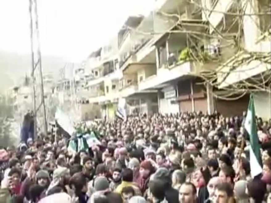 This image from amateur video made available by the Ugarit News group and shot on Jan. 29, 2012, purports to show a funeral in Damascus, Syria. The Syrian military launched an offensive to regain control of suburbs on the eastern edge of Damascus, storming neighborhoods and clashing with groups of army defectors in fierce fighting that sent residents fleeing and killed at several people, activists said. (Associated Press/Ugarit News Group via APTN)