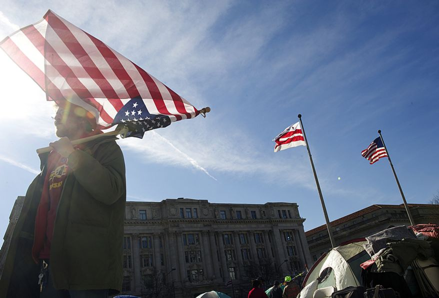 James McPherson of Norfolk, Va., holds an upside-down American flag on Jan. 30, 2012, at the Occupy D.C. encampment at Freedom Plaza in D.C. Park Police said they would begin to enforce the no-camping laws at noon that day. (Barbara L. Salisbury/The Washington Times)