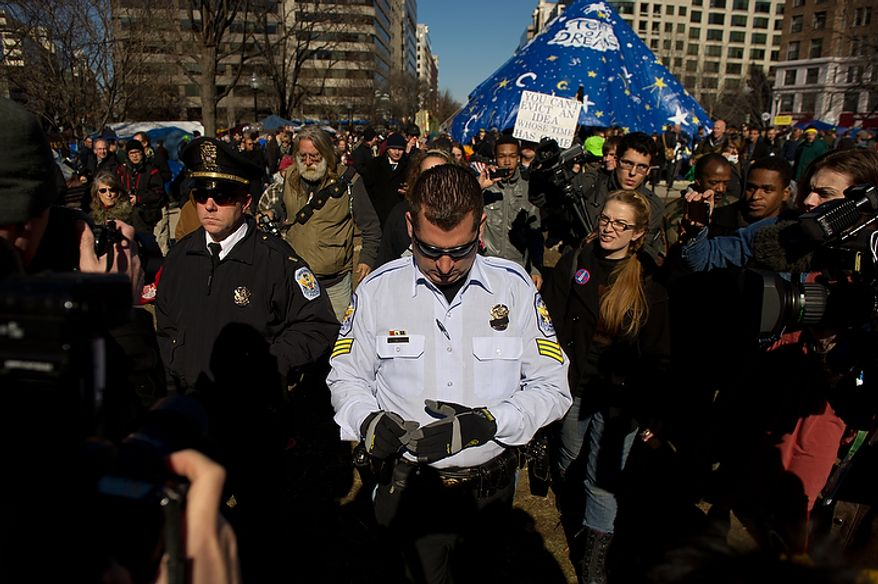 Park Police officers Lt. Steve Godfrey, left, and Sgt. Todd Reid are followed by Occupy DC protesters after they check out a large blue tarp which protesters used to cover the statue of Maj. Gen. James B. McPherson in the center of McPherson Square at noon on the day of a deadline the National Park Service set to remove camping material from McPherson Square and Freedom Plaza, Washington, DC, Monday, January 30, 2012. (Andrew Harnik / The Washington Times)