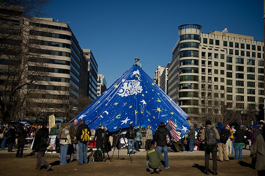 Occupy DC protesters cover the statue of Maj. Gen. James B. McPherson in the center of McPherson Square with a large blue tarp at noon on the day of a deadline the National Park Service set to remove camping material from McPherson Square and Freedom Plaza, Washington, DC, Monday, January 30, 2012. (Andrew Harnik / The Washington Times)
