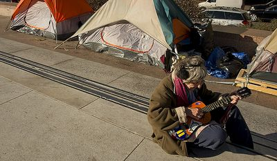 "Martha Mulligan of Washington, D.C. sings a song she wrote called ""We Need a New New Deal"" at the Freedom Plaza Occupy encampment on Monday, Jan. 30, 2012, the day that Park Police said they would begin to enforce the no camping laws. (Barbara L. Salisbury/The Washington Times)"