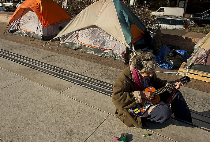 """Martha Mulligan of Washington, D.C. sings a song she wrote called """"We Need a New New Deal"""" at the Freedom Plaza Occupy encampment on Monday, Jan. 30, 2012, the day that Park Police said they would begin to enforce the no camping laws. (Barbara L. Salisbury/The Washington Times)"""