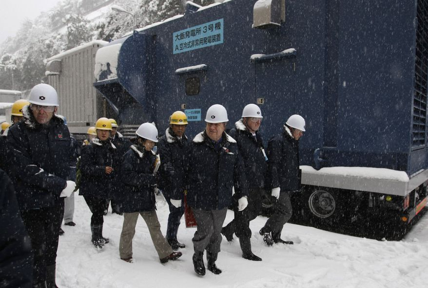 ** FILE ** International Atomic Energy Agency experts Jozef Misak (third from right) and Charles Casto (second from right) walk past an emergency air-cooled power generator as they inspect the Ohi nuclear power plant in Ohi, Fukui prefecture, Japan, on Thursday, Jan. 26, 2012. (AP Photo/Shizuo Kambayashi, File)