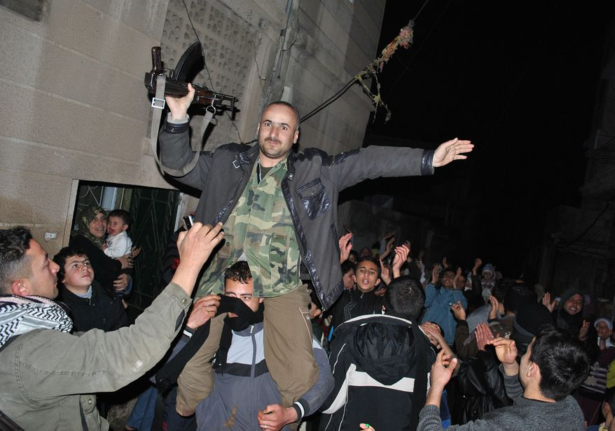 Anti-regime protesters hold up a Syrian army defector as they chant slogans against Syrian President Bashar Assad during an evening protest in the Rastan area of Syria's Homs province on Monday, Jan. 30, 2012. (AP Photo)