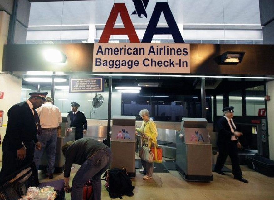American Airlines baggage handlers help passengers check luggage Wednesday at Dallas-Fort Worth International Airport in Grapevine, Texas. American's corporate leadership is having closed-door meetings with union representatives about the future of employees' jobs and pensions. (Associated Press)