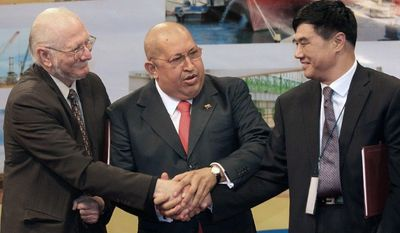 Celebrating at a November signing ceremony in Caracas, (from left) are Jorge Giordani, Venezuela's minister of planning and finance; President Hugo Chavez; and Zhan Xiaoquiang, China's vice minister of national development and reform. (Associated Press)
