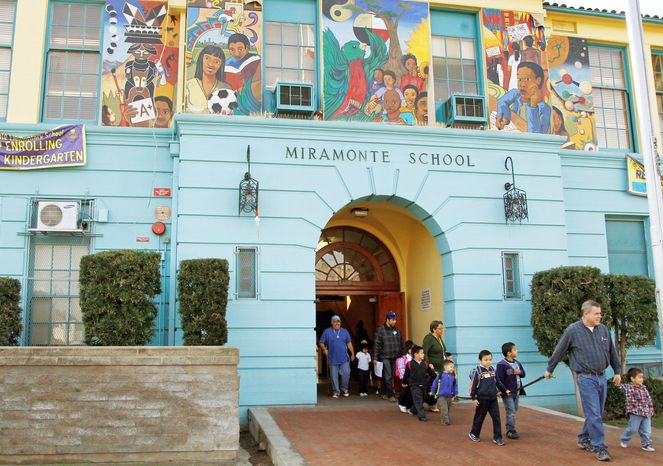 Students are escorted to the bus Tuesday as they leave Miramonte Elementary School in Los Angeles. (Associated Press)