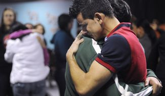 International Church of the Restoration parishioners in Marietta, Ga., mourn Jan. 30, 2012, the loss of Pastor Jose Carmo Jr., his wife Adriana and their daughter Leticia Carmo, who were killed the previous day in a multi-vehicle crash on Interstate 75 in Florida. (Associated Press)