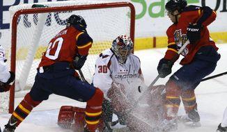 Washington Capitals goalie Michal Neuvirth (30) blocks a shot by Florida Panthers center Mike Santorelli, right, as Panthers' Sean Bergenheim (20) tries to get control of the rebound during the first period of an NHL hockey game in Sunrise, Fla., Wednesday, Feb. 1, 2012. (AP Photo/Alan Diaz)