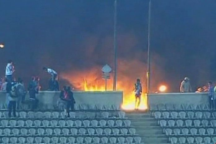 This image made from Egypt TV shows fans and a fire on Feb.1, 2012, at a soccer stadium in Port Said, Egypt. Dozens of Egyptians were killed in violence following a soccer match when fans flooded the field seconds after the match against a rival team was over, Egypt's health ministry said. (Associated Press/Egypt TV via APTN)