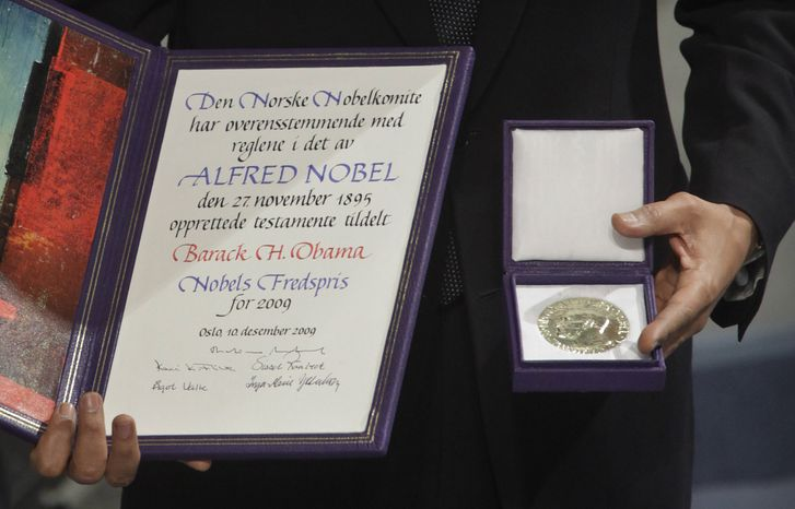 **FILE** President Obama, a 2009 Nobel Peace Prize laureate, poses Dec. 10, 2009, with his medal and diploma at the prize ceremony at City Hall in Oslo. (Associated Press)