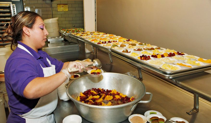 Vivan Perez dishes out fruit for lunch at Kepner Middle School in Denver. The Colorado General Assembly is considering the nation's toughest ban on unhealthy fats that would apply to food served in school and after school. (Associated Press)
