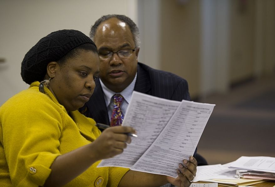 Ward 7 resident Dawn Matthews, left, and her assistant Kemry Hughes look over what they consider to be suspect petition signatures collected to add Yvette Alexander's name to the ballot for Ward 7 council. Ms. Matthews and Mr. Hughes were part of a D.C. Board of Elections and Ethics hearing Thursday, Feb. 2, 2012, in Washington, D.C. Ms. Matthews is asking that Ms. Alexander's name be removed from the ballot. (Barbara L. Salisbury/The Washington Times)