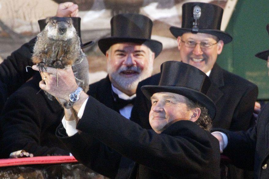 Groundhog Club handler John Griffiths holds Punxsutawney Phil, the weather-prognosticating groundhog, during the 126th celebration of Groundhog Day on Gobbler's Knob in Punxsutawney, Pa., on Thursday, Feb. 2, 2012. Phil saw his shadow, forecasting six more weeks of winter weather. (AP Photo/Gene J. Puskar)